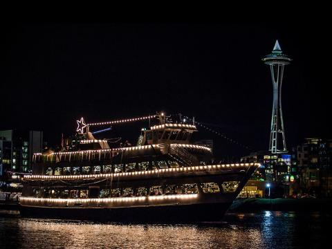 A decked-out ship floating in front of the Space Needle during Argosy Christmas Ships & Bonfires