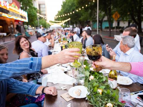 Dining on Stockton's Main Street at a long outdoor table during the farm-to-table Feast at the Fox event